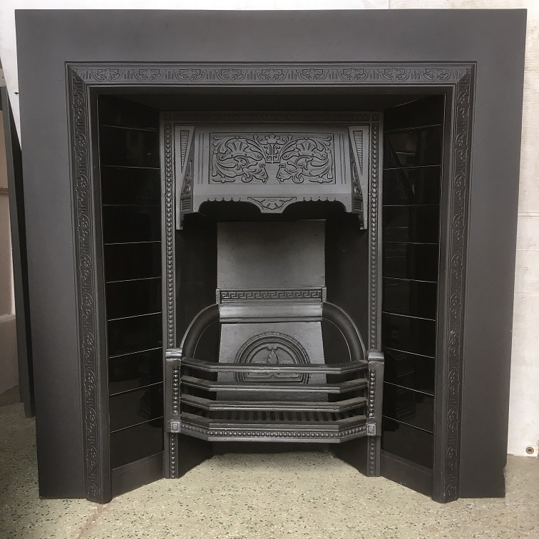 example of restored original cast iron fireplace insert with gloss black fireplace tiles