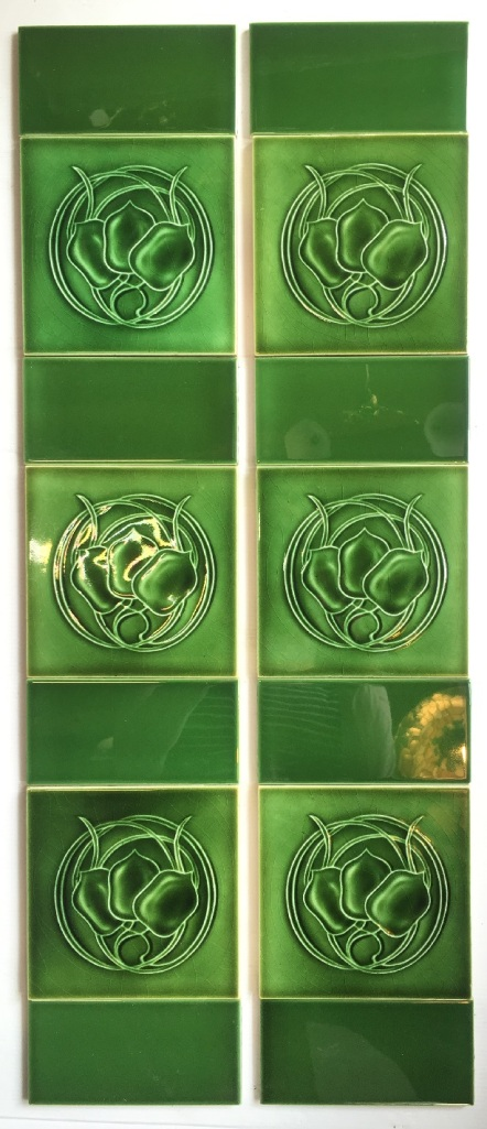 Art Nouveau feature tiles 6 x 6 inch, circa 1905, monochrome green glaze, three stylised flowers in circular foliage, two panel fireplace tile set, $325 OTB 28