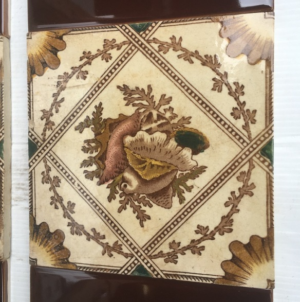 Detail of late 1800s Aesthetic, seashell design feature tiles, teapot brown print with hand tinting on white clay ground.