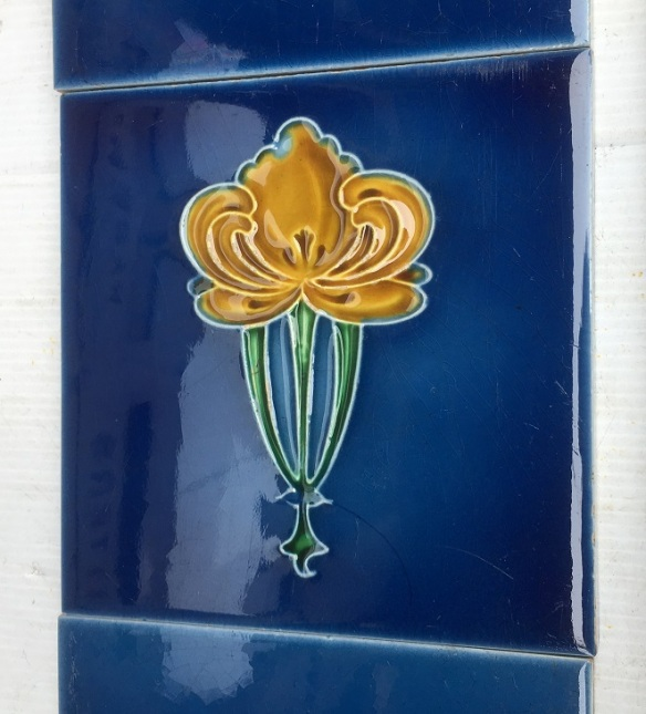 Original moulded majolica tiles, unusual royal blue glaze with stylised yellow flower, two panel fireplace set $195 OTB 86 salvaged, vintage recycled, demolition, reproduction, restoration, home renovation secondhand, used , original, old, reclaimed, heritage, antique, victorian, art nouveau edwardian, georgian, art decoDetail of Deco style lettering to pub door