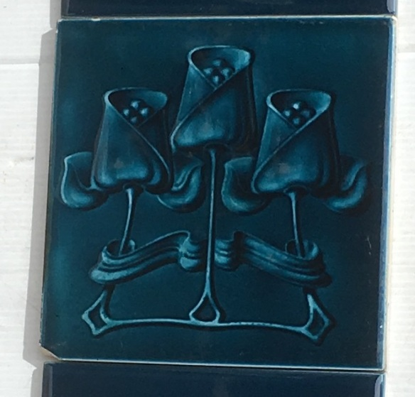 detail of Original Art Nouveau feature tiles T and R Boote, England c 1905, trio of stylised tulips, moulded tile with midnight blue glaze, two panel fireplace set, can be separated into pair $340 SET 211 salvaged, recycled, demolition, reproduction, restoration, renovation,collectable, secondhand, used , original, old, reclaimed, heritage, antique, victorian, art nouveau edwardian, georgian, art deco