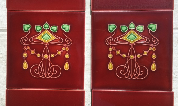 Detail of Circa 1899 Lea and Boulton Jewel tiles 6x6 inch with Sherwin moulded 3 x 6 tiles in rich burgundy wijth green and yellow, two panel fireplace set, $400 OTB 113 salvaged, vintage recycled, demolition, reproduction, restoration, home renovation secondhand, used , original, old, reclaimed, heritage, antique, victorian, art nouveau edwardian, georgian, art decoDetail of Deco style lettering to pub door