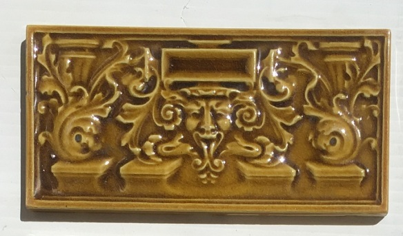 Detail of circa 1900 original English 6 x 3 inch feature tiles, moulded, satyr face with Baroque scrolls, amber glaze, 5 available, $20 each WSsalvaged, recycled, demolition, reproduction, restoration, home renovation secondhand, used , original, old, reclaimed, heritage, antique, victorian, art nouveau edwardian, georgian, art deco